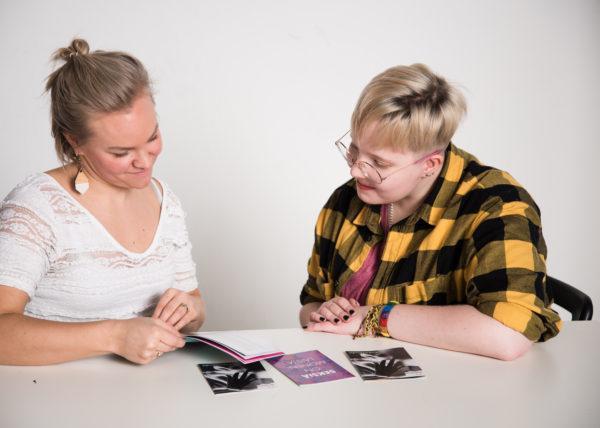 Seksuaalikasvatus käynnissä. Kuvassa aikuinen ja nuori tutkivat seksuaalikasvatuksen ja seksuaaliterveyden esitteitä.