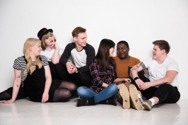 Kuvassa joukko eri näköisiä nuoria juttelee lattialla istuen. Seksuaalikasvatus ja Veckan sex eli 5 vinkkiä