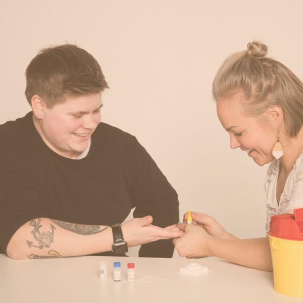 Kuvassa kaksi henkilöä tekemässä hiv-testiä. Terveydenhoitajapäivät Rovaniemi 2019.