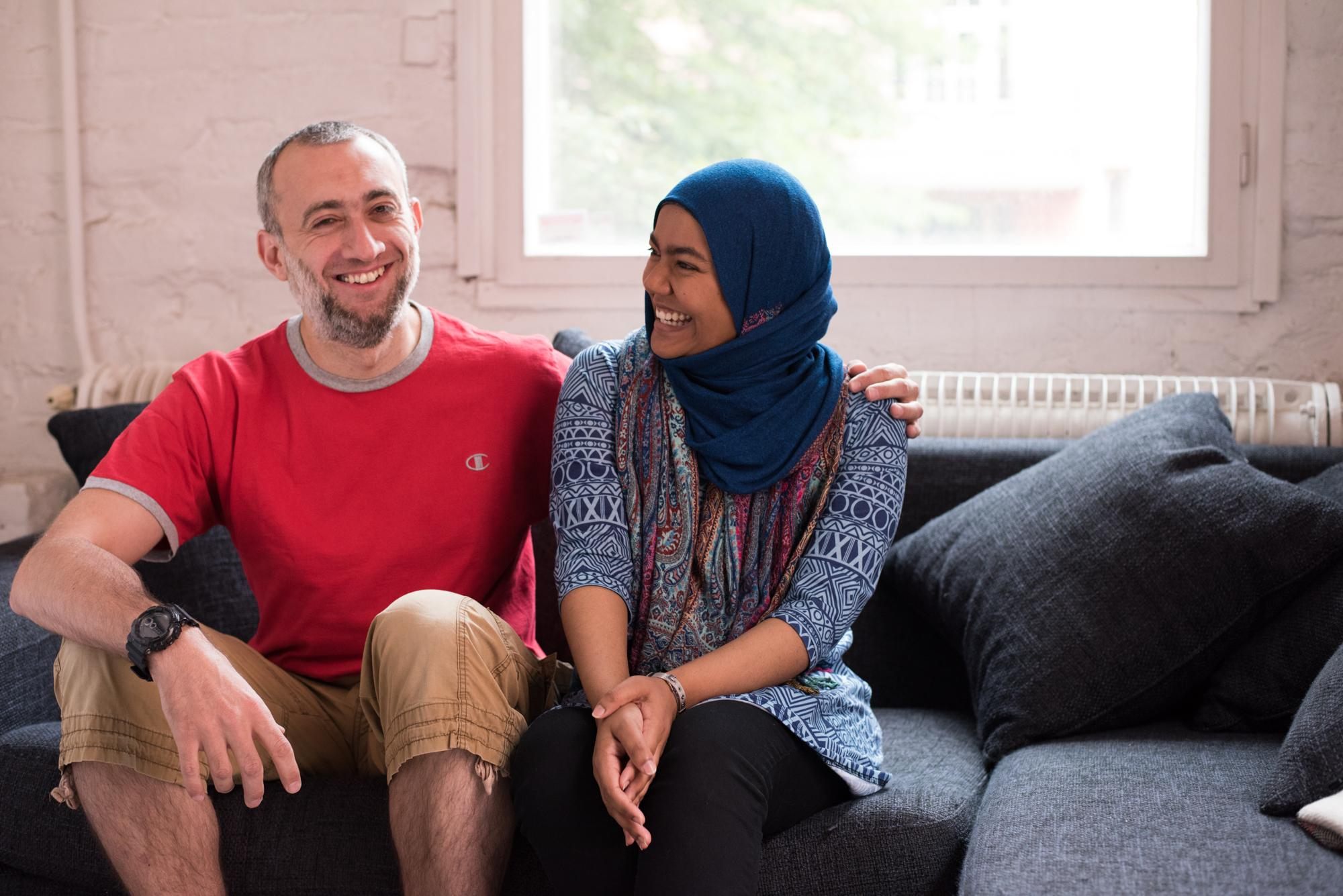 Kaksi henkilöä istuvat sohvalla ja nauravat yhdessä.