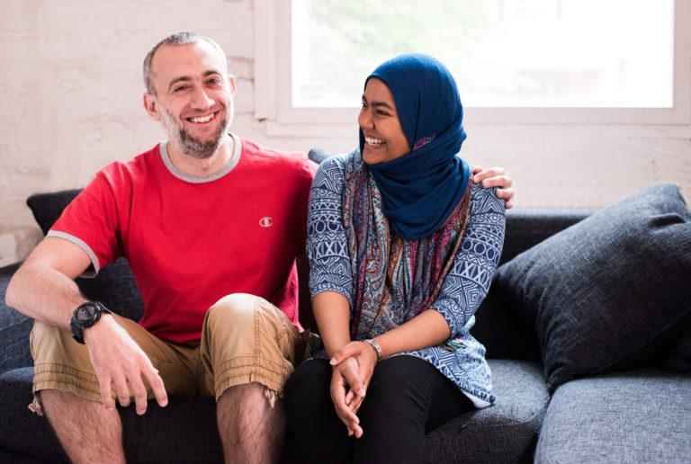 Kuvassa kaksi ihmistä istuu sohvalla vierekkäin ja hymyilevät toisilleen.