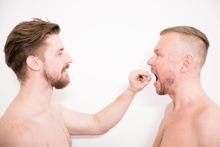 Kuvassa on kaksi paidatonta henkilöä, joista toinen on syöttämässä toiselle prep-lääkettä.