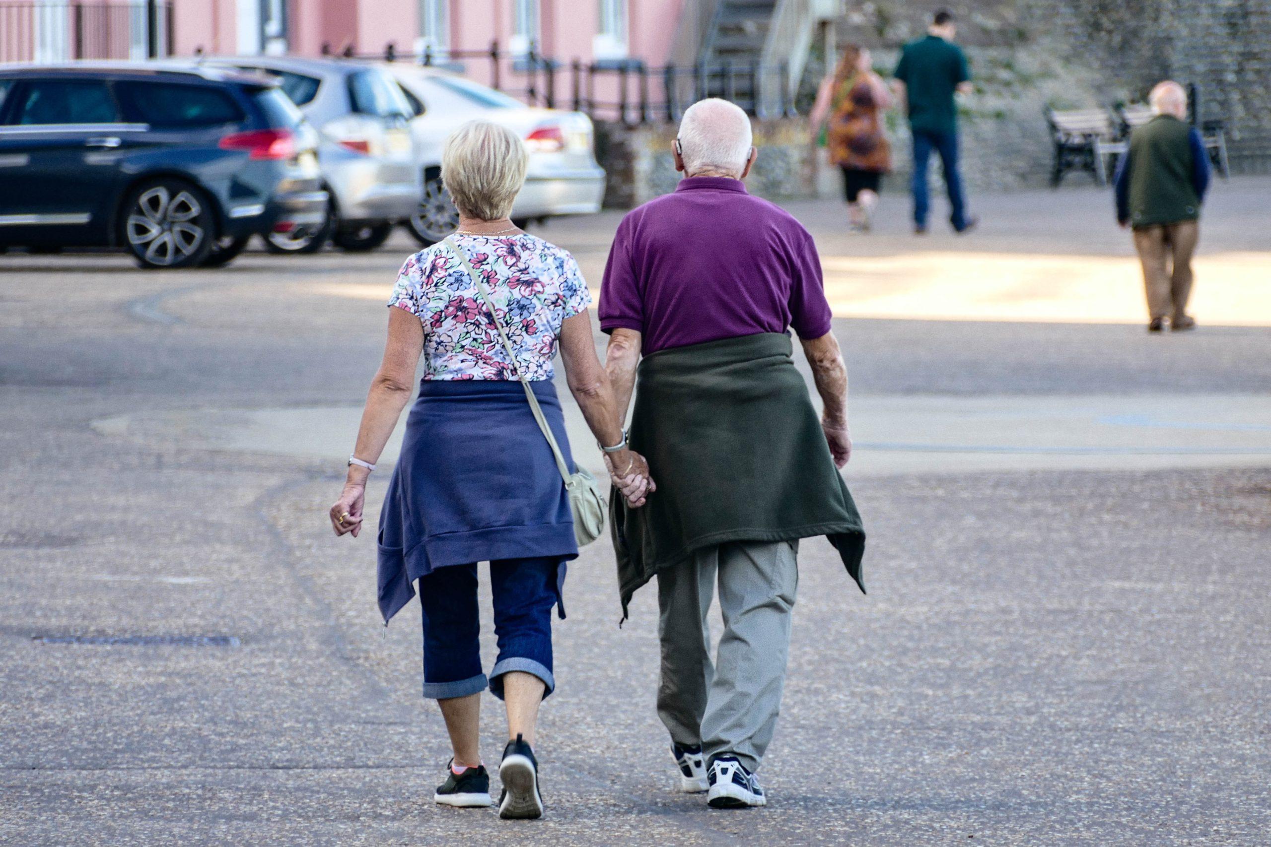 Kaksi ikääntyvää henkilöä kävelevät käsi kädessä