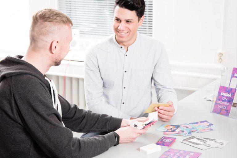 Kuvassa hivpointin työntekijä keskustelee asiakkaan kanssa esitteiden äärellä. Neuvontapalveluina hivpointilla myös puhelinneuvonta ja chat.