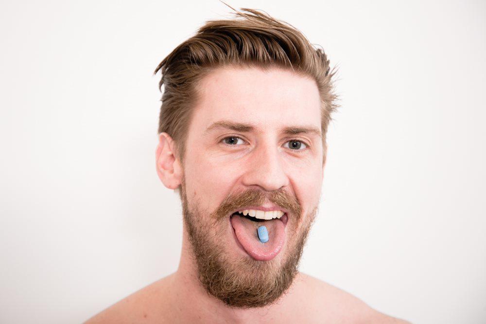 Kuvassa henkilön kasvot. Hän pitää suutaan auki ja hänen kielellään on sininen lääketabletti.