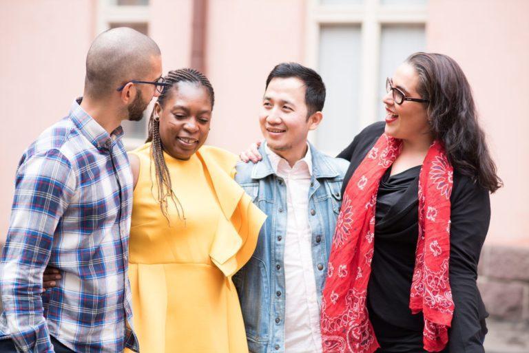 Hivpointin vertaistukiryhmä on luottamuksellinen keskusteluympäristö. Kuvassa neljä henkilöä keskustelevat ja hymyilevät toisilleen.