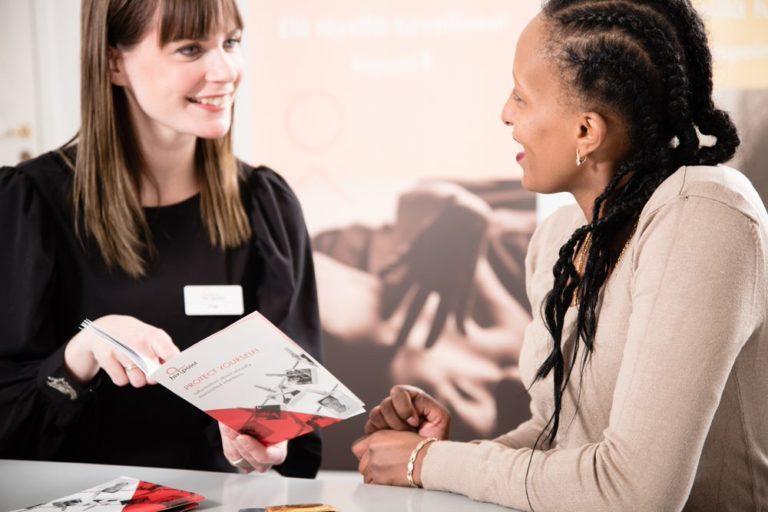 Haluatko hivpointin vapaaehtoiseksi? Kuvassa kaksi henkilöä keskustelee iloisesti Hivpointin esitteestä.