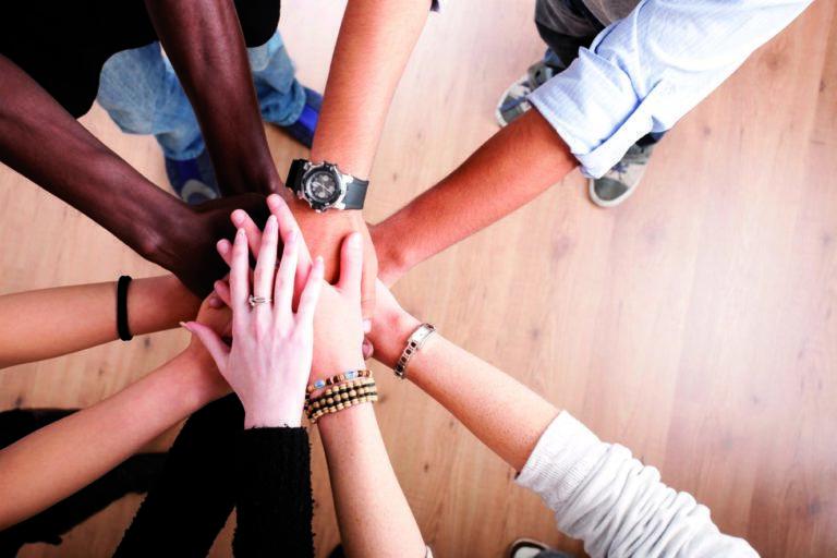 Hivpointin kurssit auttavat ammattilais- ja vertaistuen keinoin. Kuvassa viisi ihmistä pitää käsiään yhdessä.