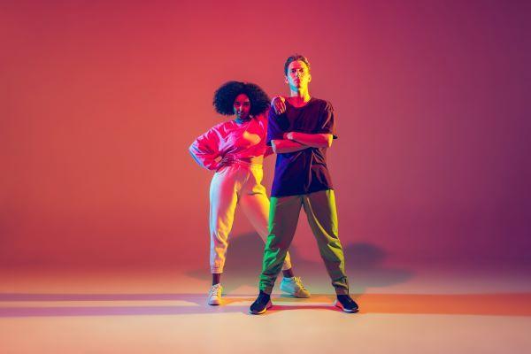 Kaksi nuorta ihmistä seisoo virekkäin ja katsoo kameraan