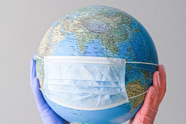 kuvassa kaksi suojakäsinein peitettyä kättä kannattelee maapalloa, jonka päälle on puettu kasvomaski