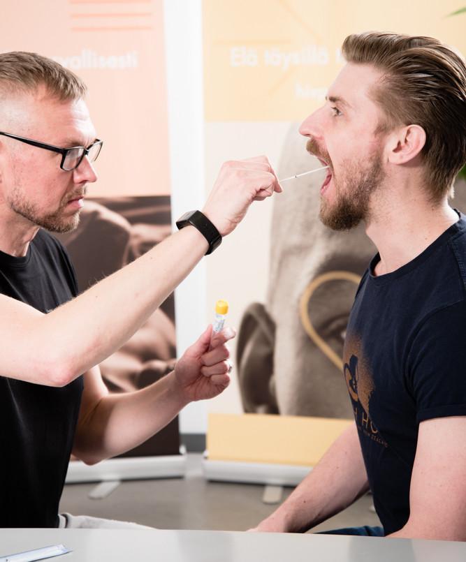 Hivpointin työntekijä ottaa nielunäytettä toisen henkilön suun limakalvoilta